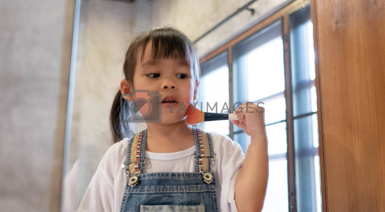 Cute little girl doing makeup and having fun brushing on cheek at a mirror in room.