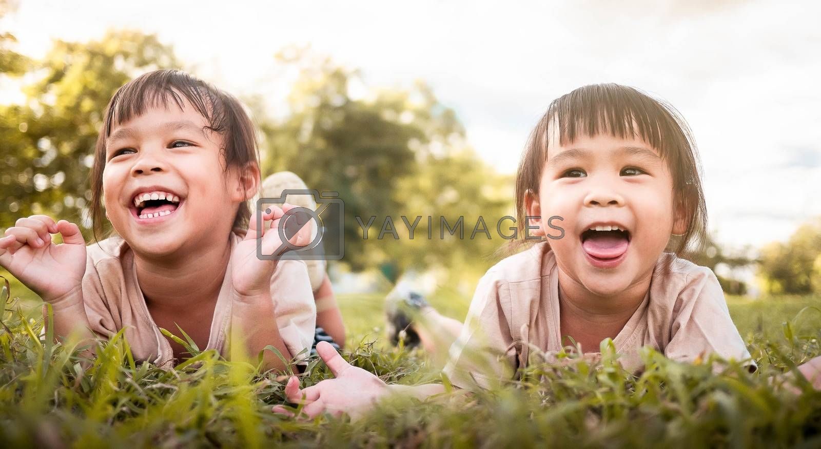 Two happy sibling girls lying on green grass outdoors in summer park.