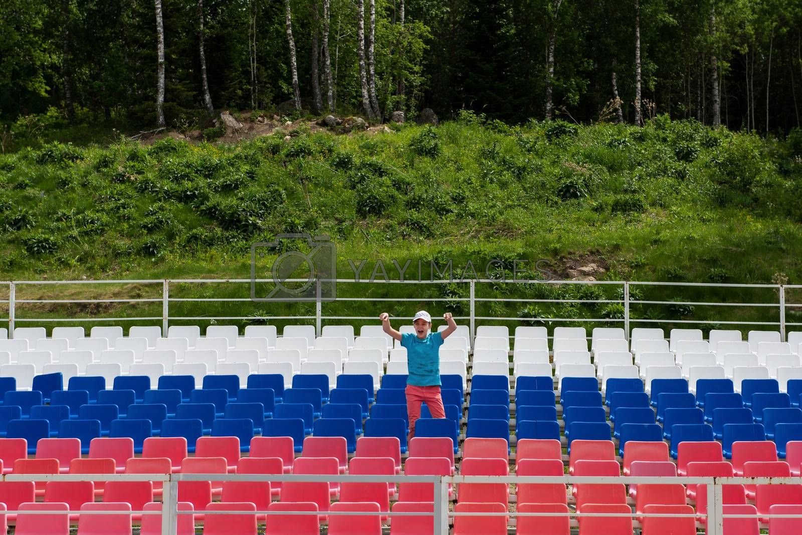 Lonely boy on the empty stadium outdoor. Empty tribune due to pandemic Covid-19. Concept of pandemic life , empty stadiums, distance from viewers, safety.