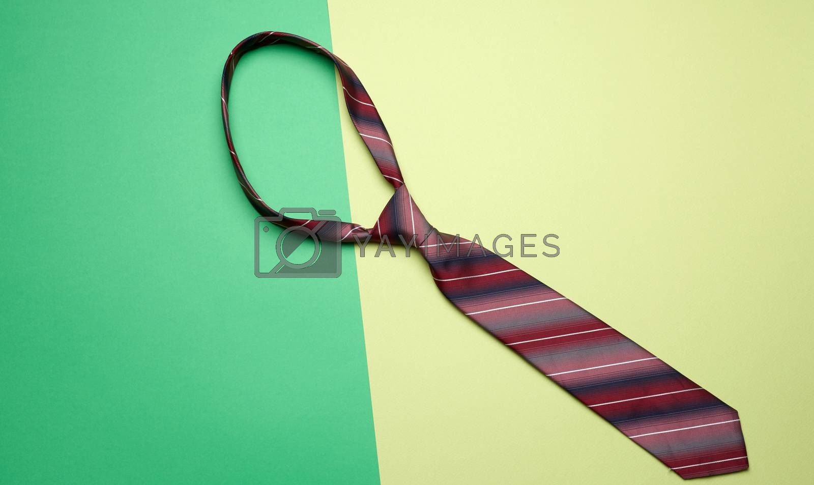 knotted silk man's tie on a green background, top view