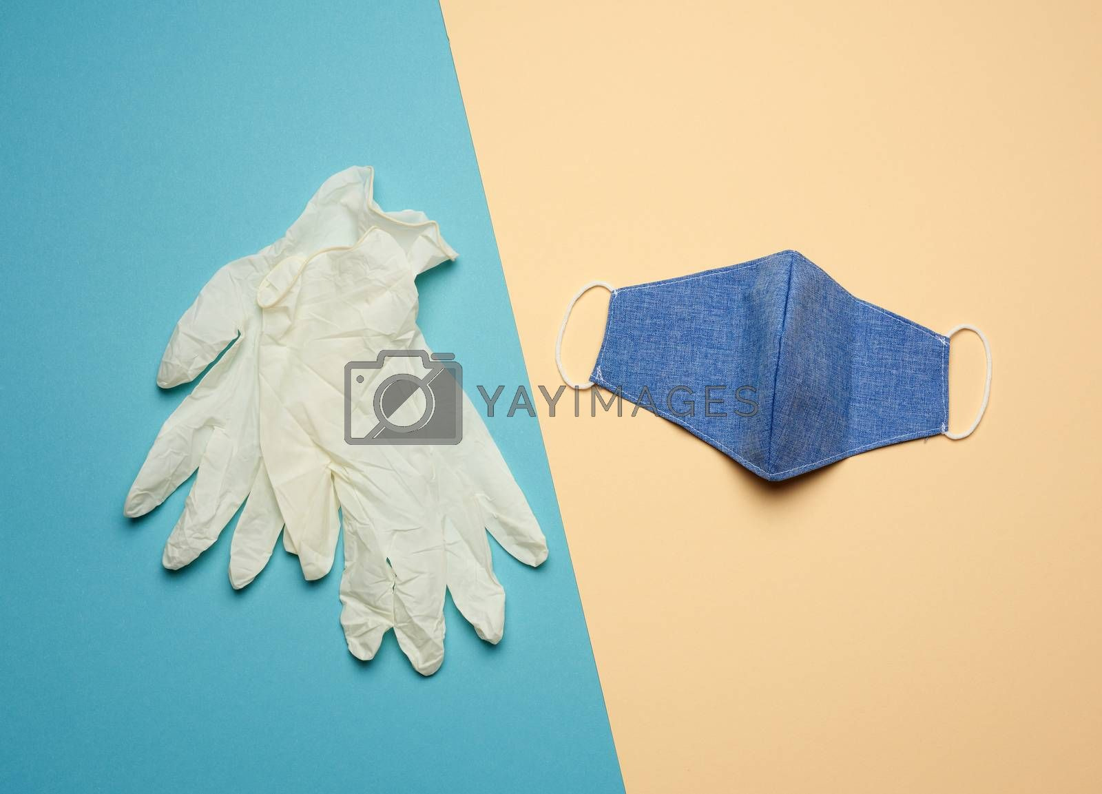 white latex gloves and blue reusable textile mask on a blue beige background, hygiene and virus protection accessories for epidemics and pandemics, overhead view