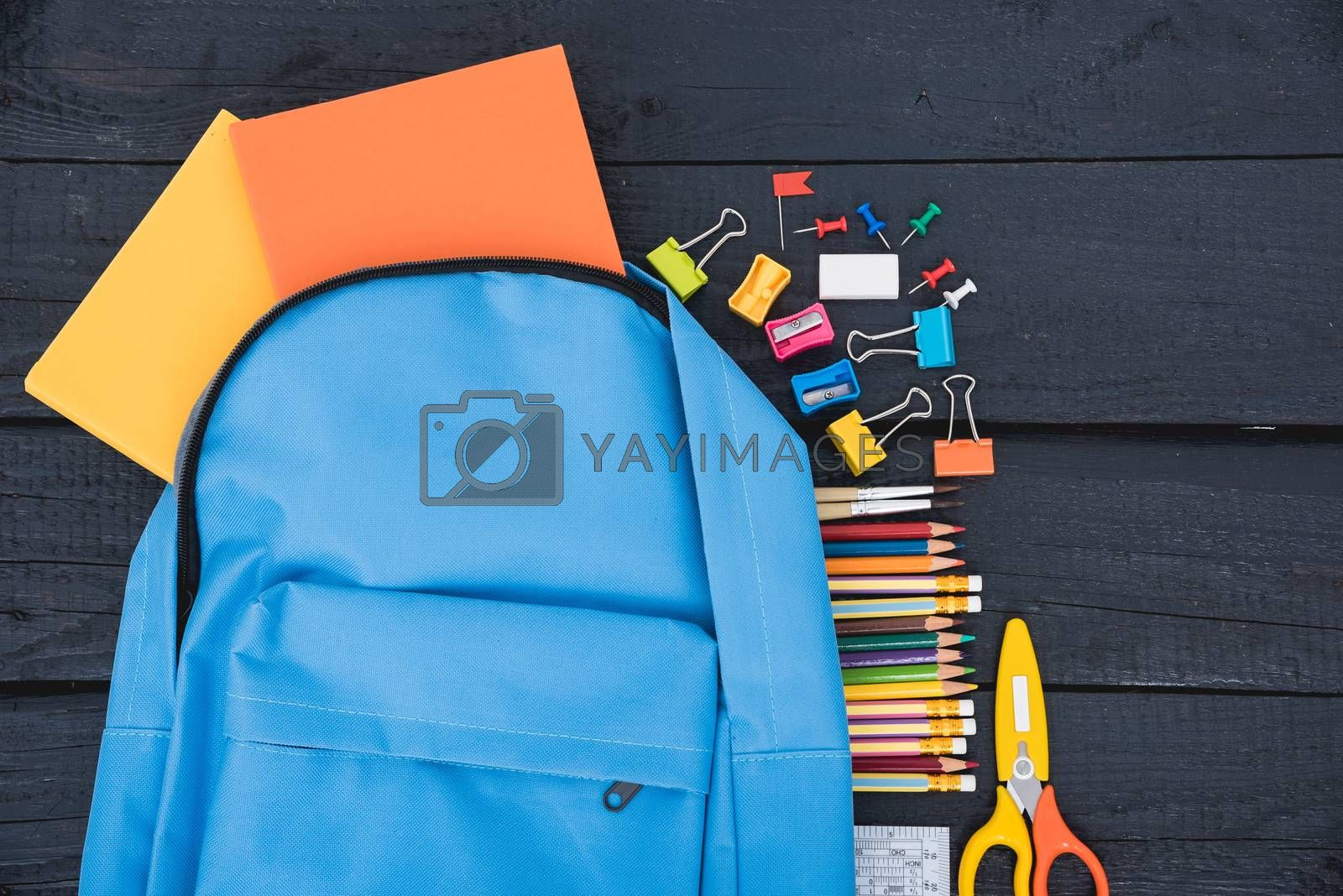 Top view flat lay of blue school bag backpack and accessories tools for children education on black wood background, Back to school concept and have copy space for use