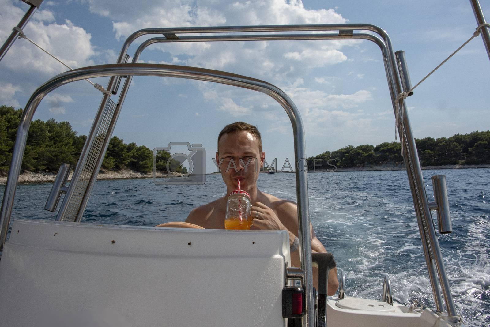 Croatia, Hvar - June 2018: Caucasian man, mid 40's drives a small boat on vacation