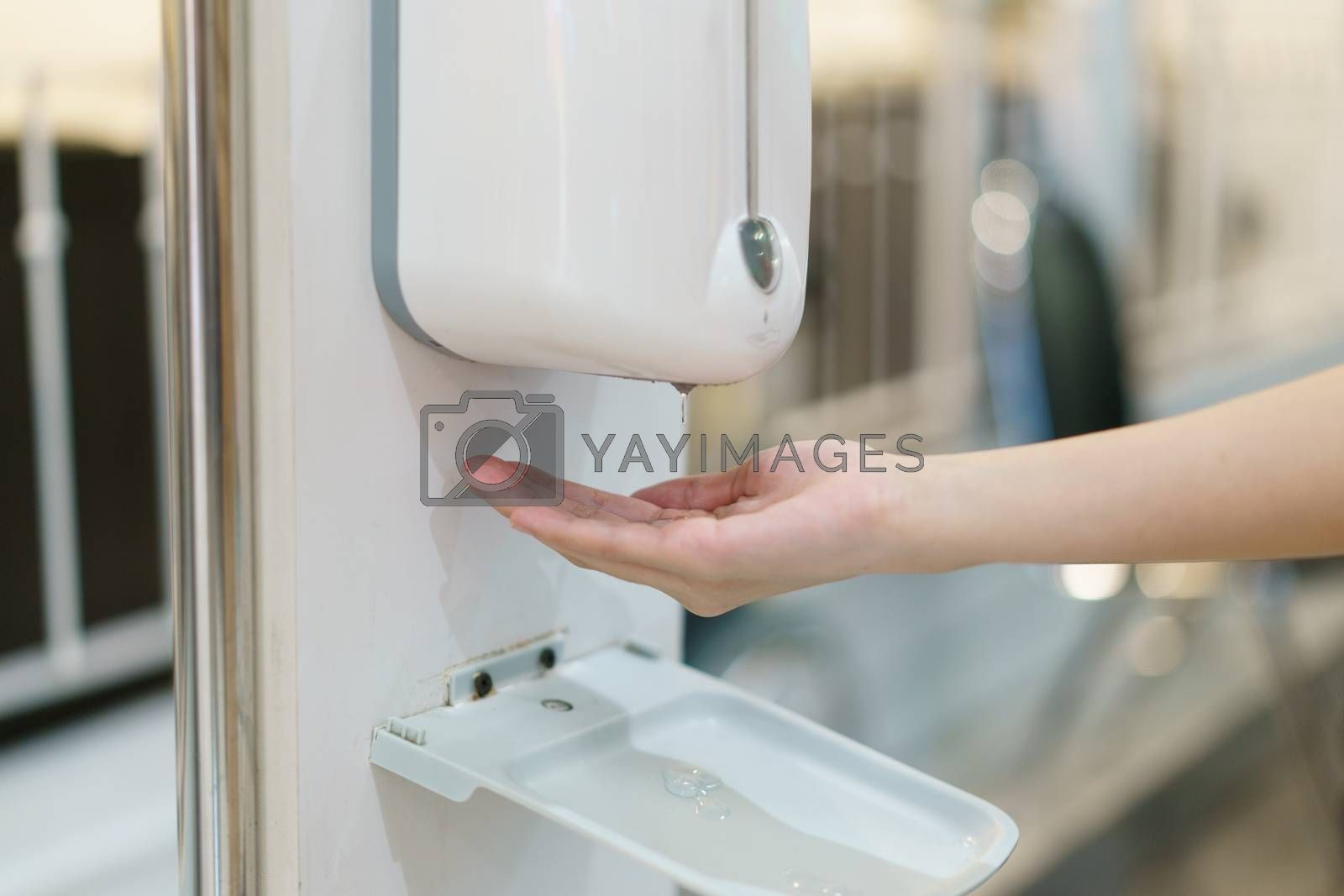 Hands with automatic sanitizer liquid spray machine, touchless dispenser.