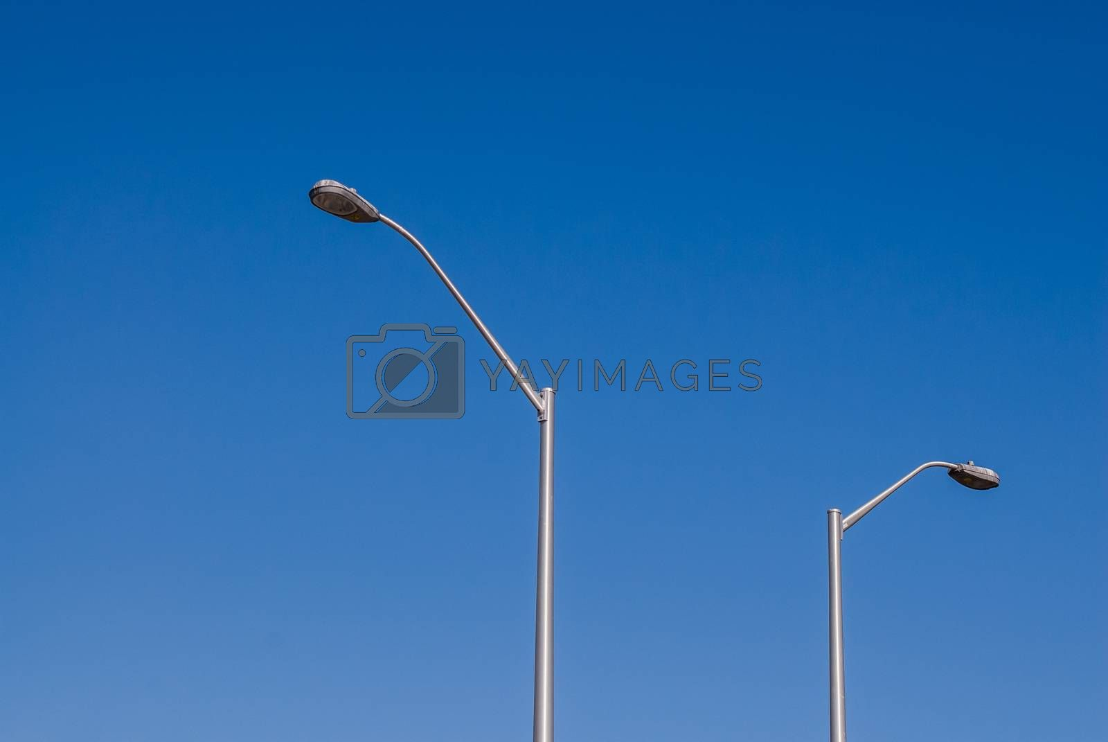 Two tall metallic street lights against clear empty blue sky.
