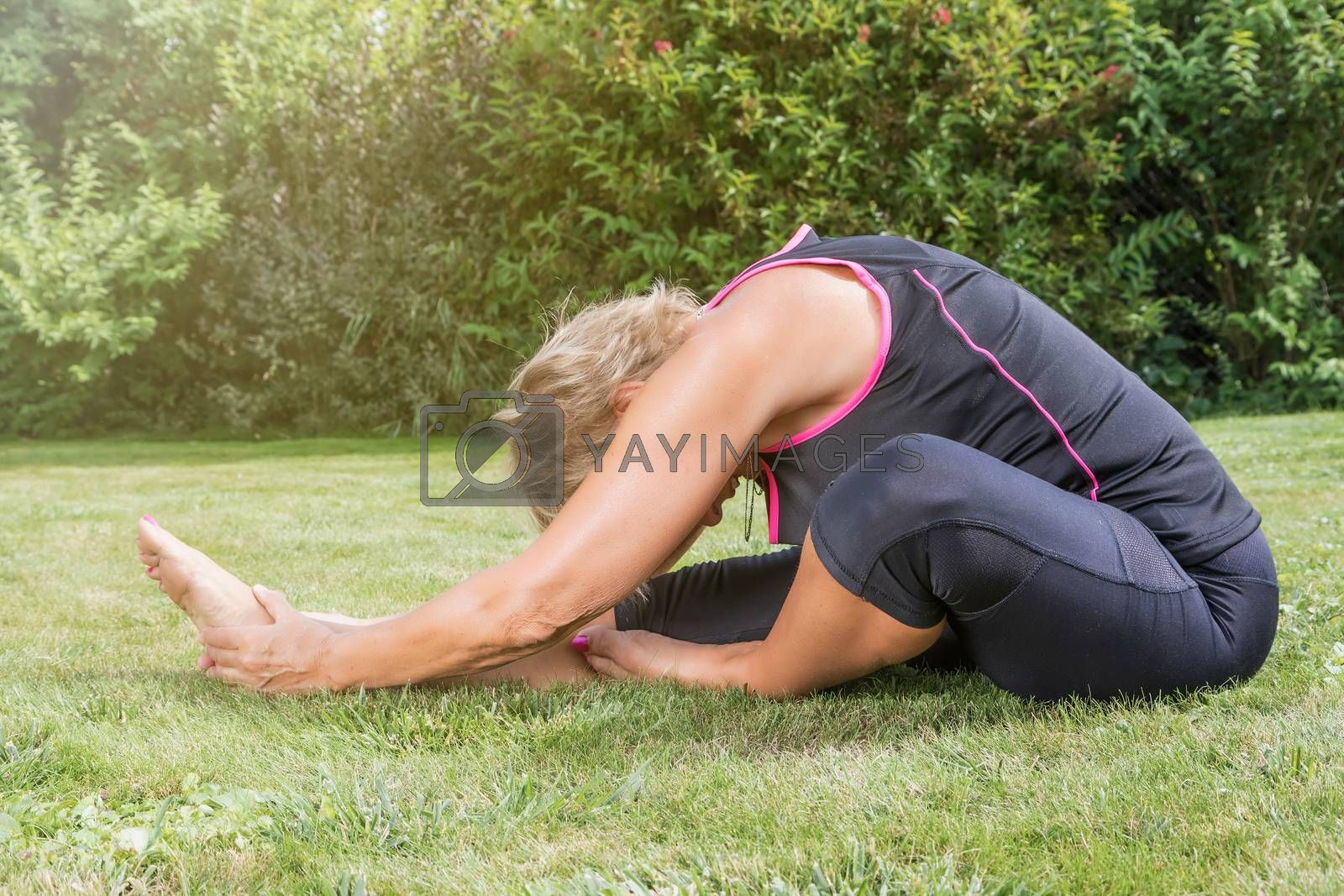 Attractive senior blond woman in yoga head to knee pose in the garden.