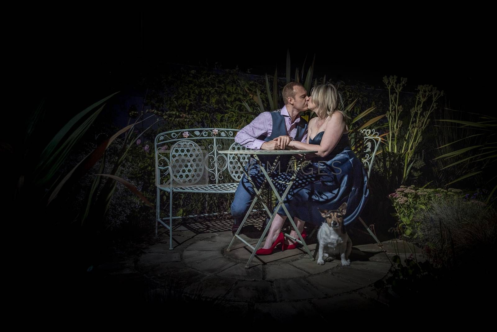 Quorn, UK - Aug 2019: Couple kissing on a garden bench at night, dog in forground