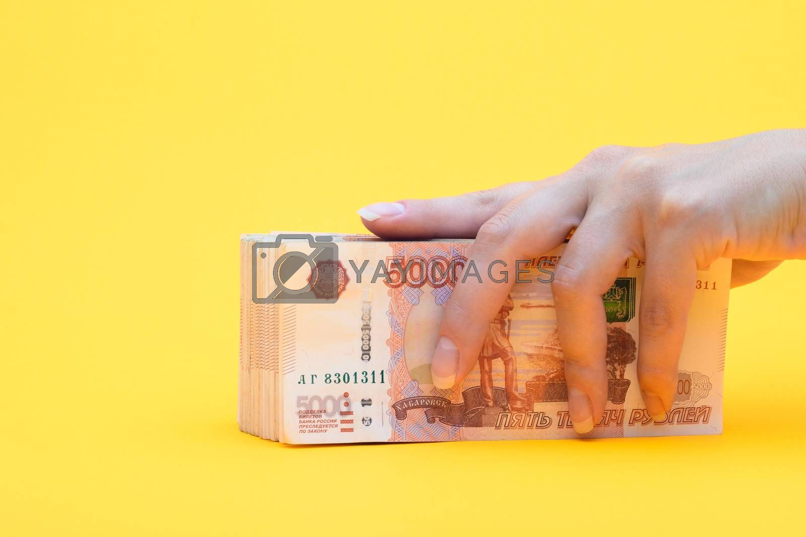 Hand covered a pack of five thousandth bills, yellow background