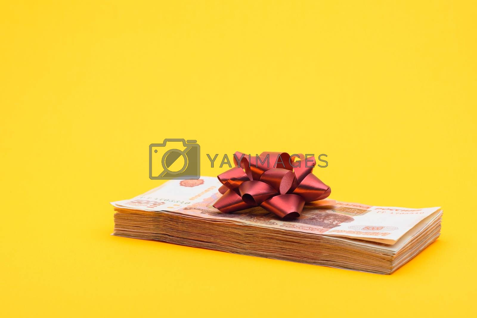 On the bundle of five thousandth bills lies a red bow, yellow background
