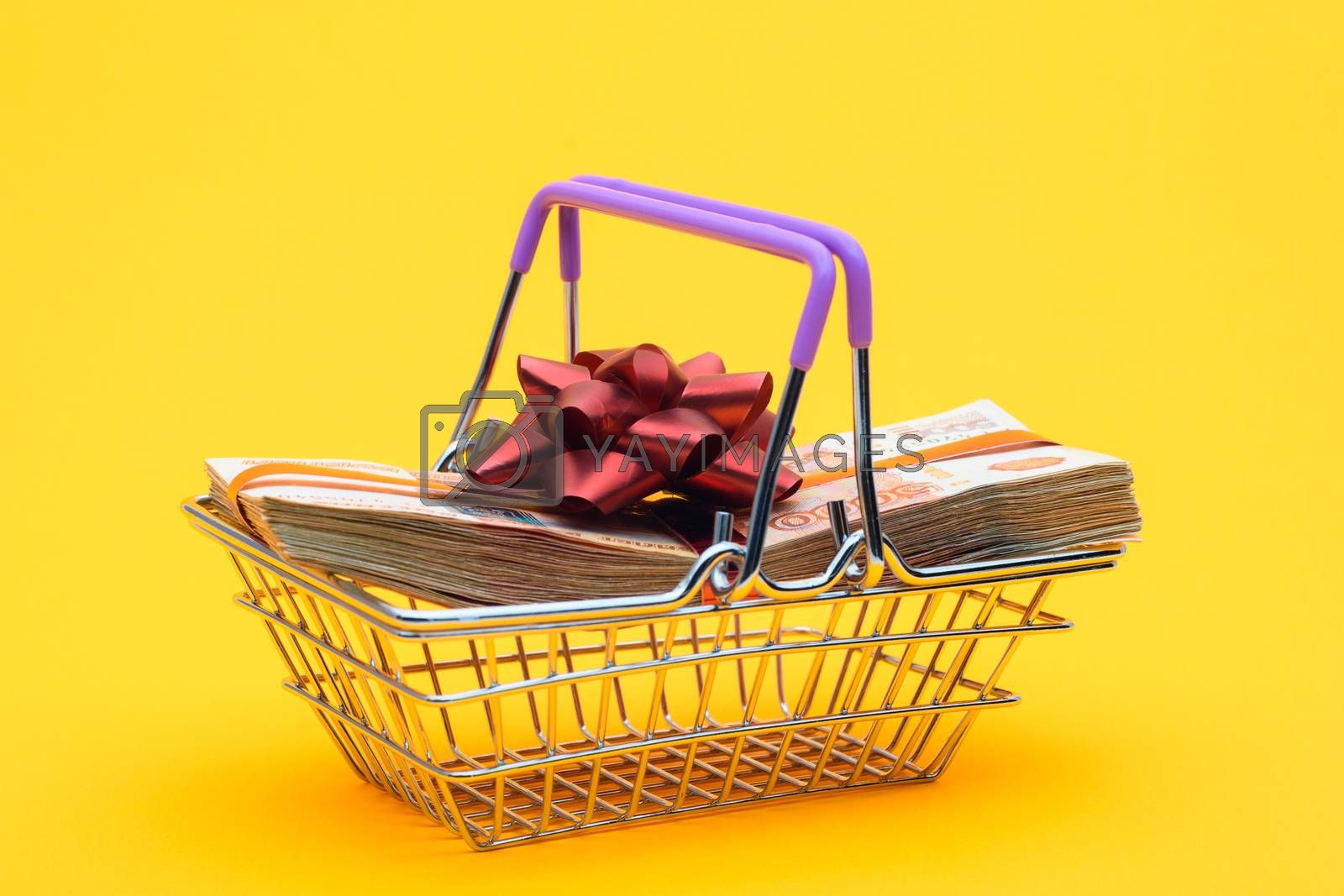 In the grocery basket is a bundle of money with a red bow
