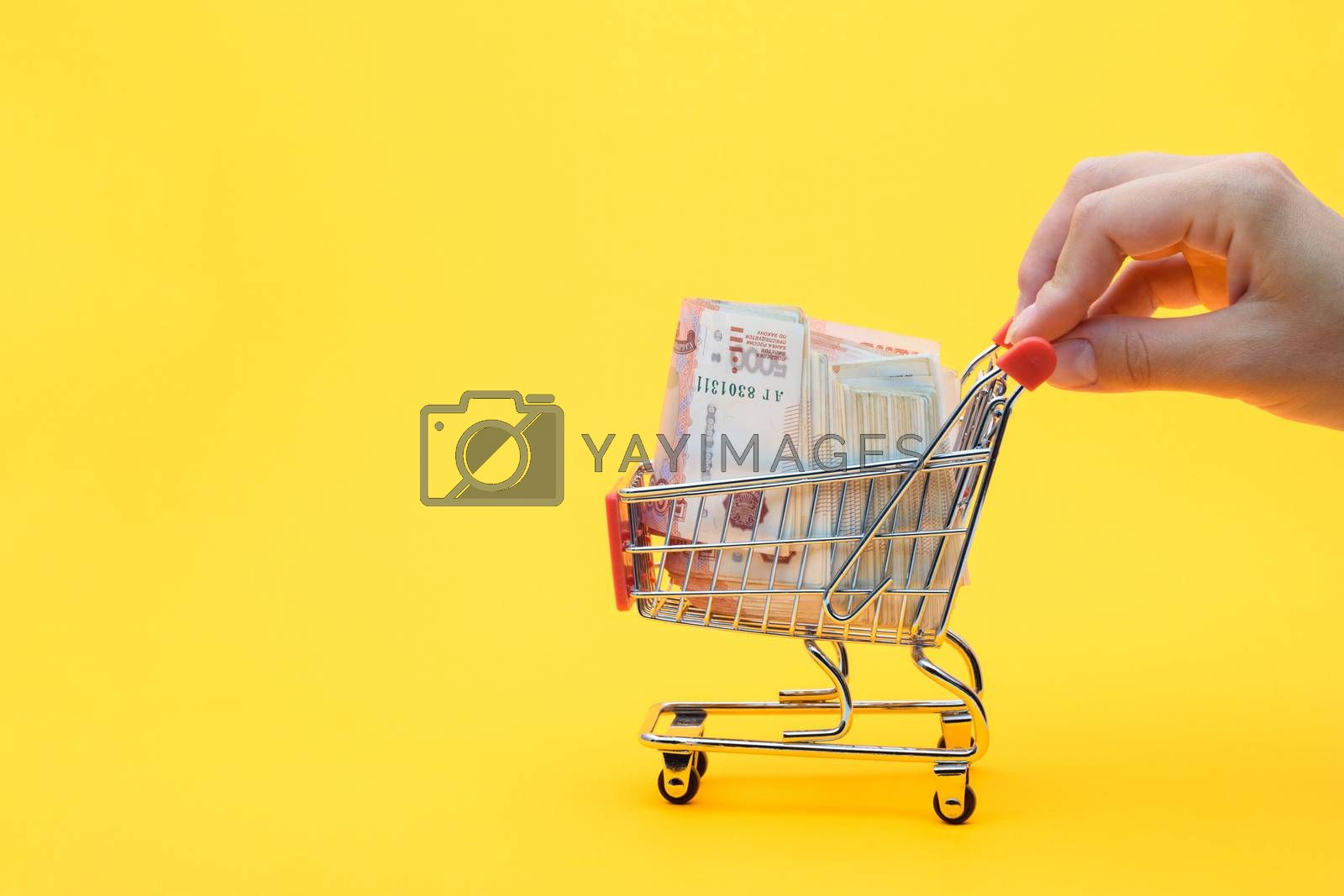Hand carries a grocery cart with a pack of five thousandth Russian rubles