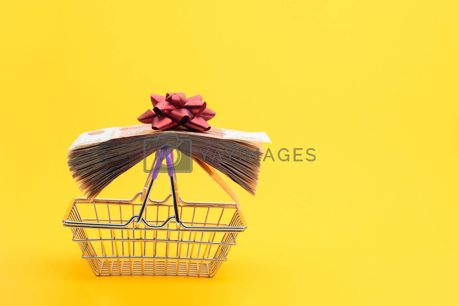 On the handles of the grocery cart lies a bundle of notes packed with gift ribbon and a red bow