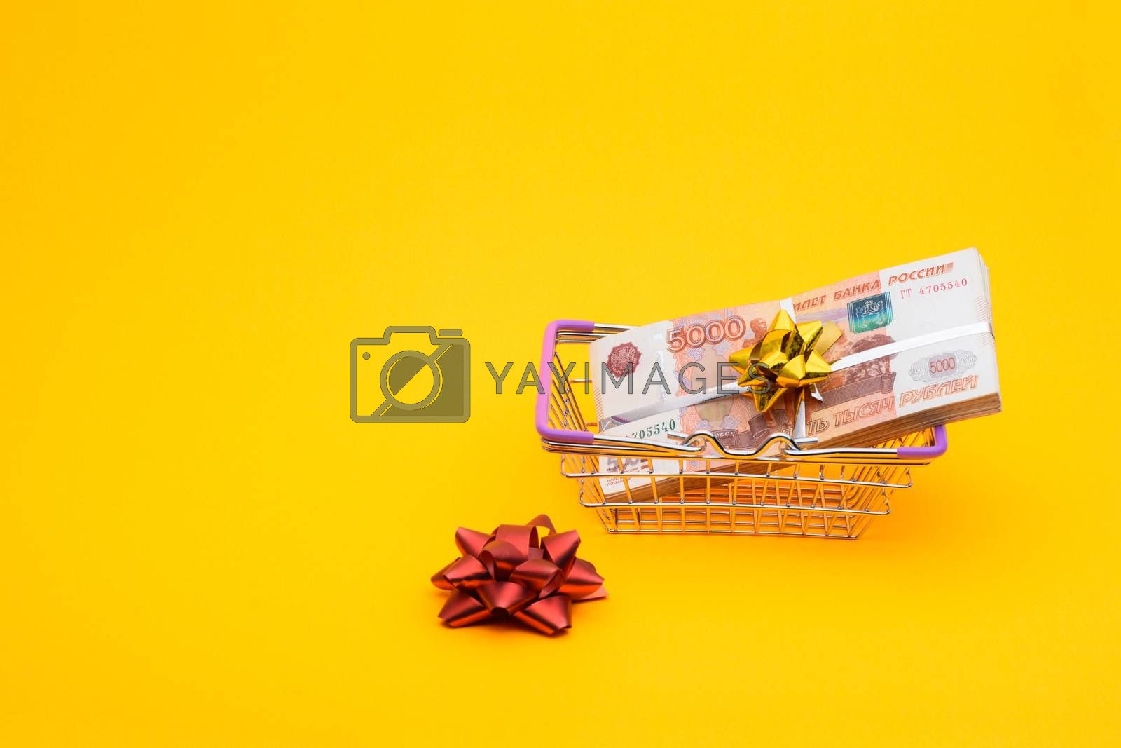 In the grocery basket is a bundle of five thousandth bills, next to it is a red bow
