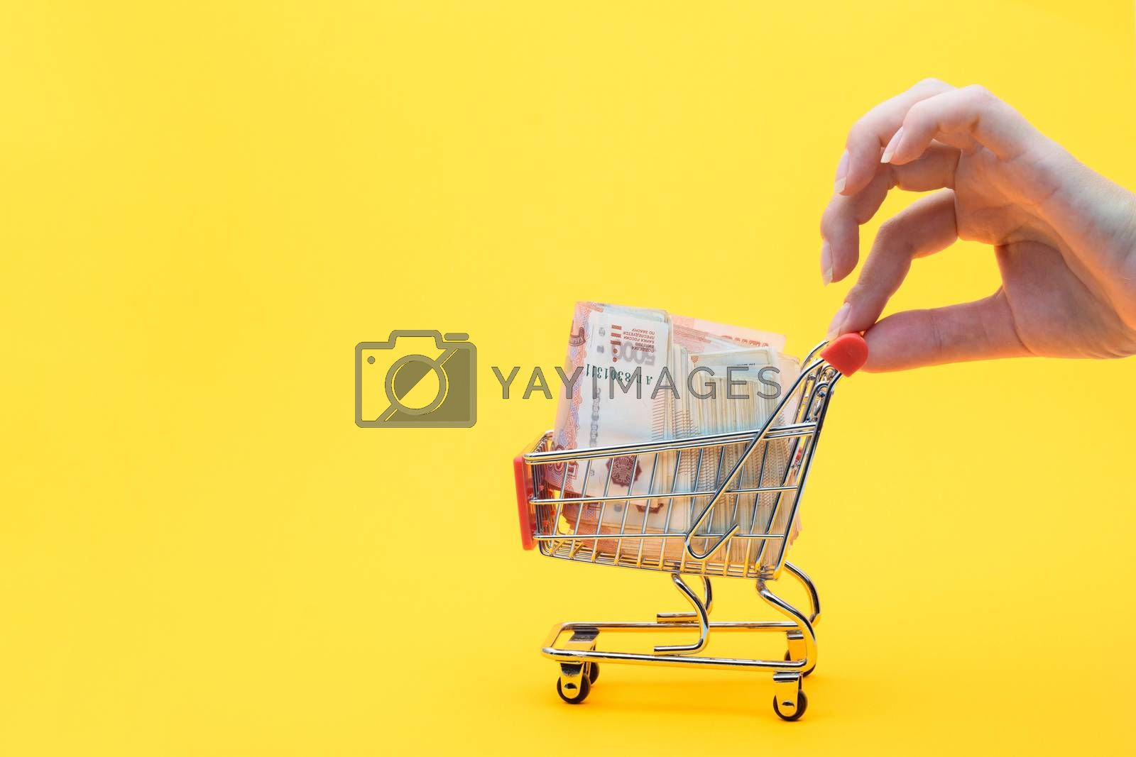 Hand holds the handle of a grocery cart with a pack of five thousandth Russian rubles, yellow background