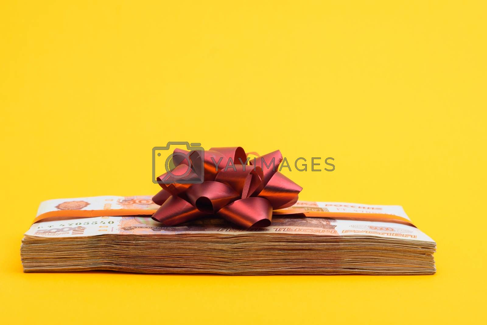A bundle of money tied with ribbons and bow on a yellow background