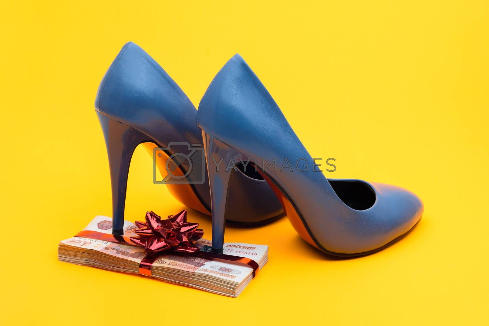 On a gift pack of five thousandth notes are women's blue high-heeled shoes