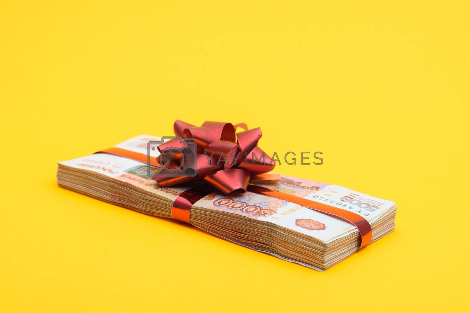 On a yellow background lies a gift pack of five thousandth Russian bills