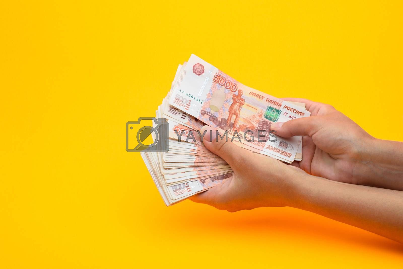 In hands lies a bundle of five thousandth bills on a yellow background