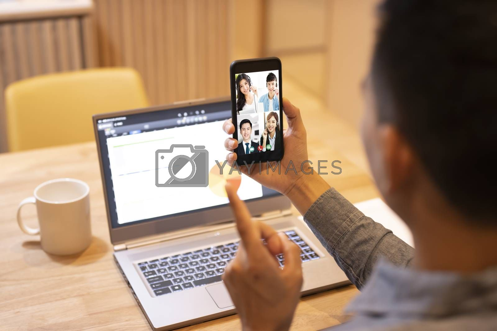 young man working at home and using smart phone with video conference
