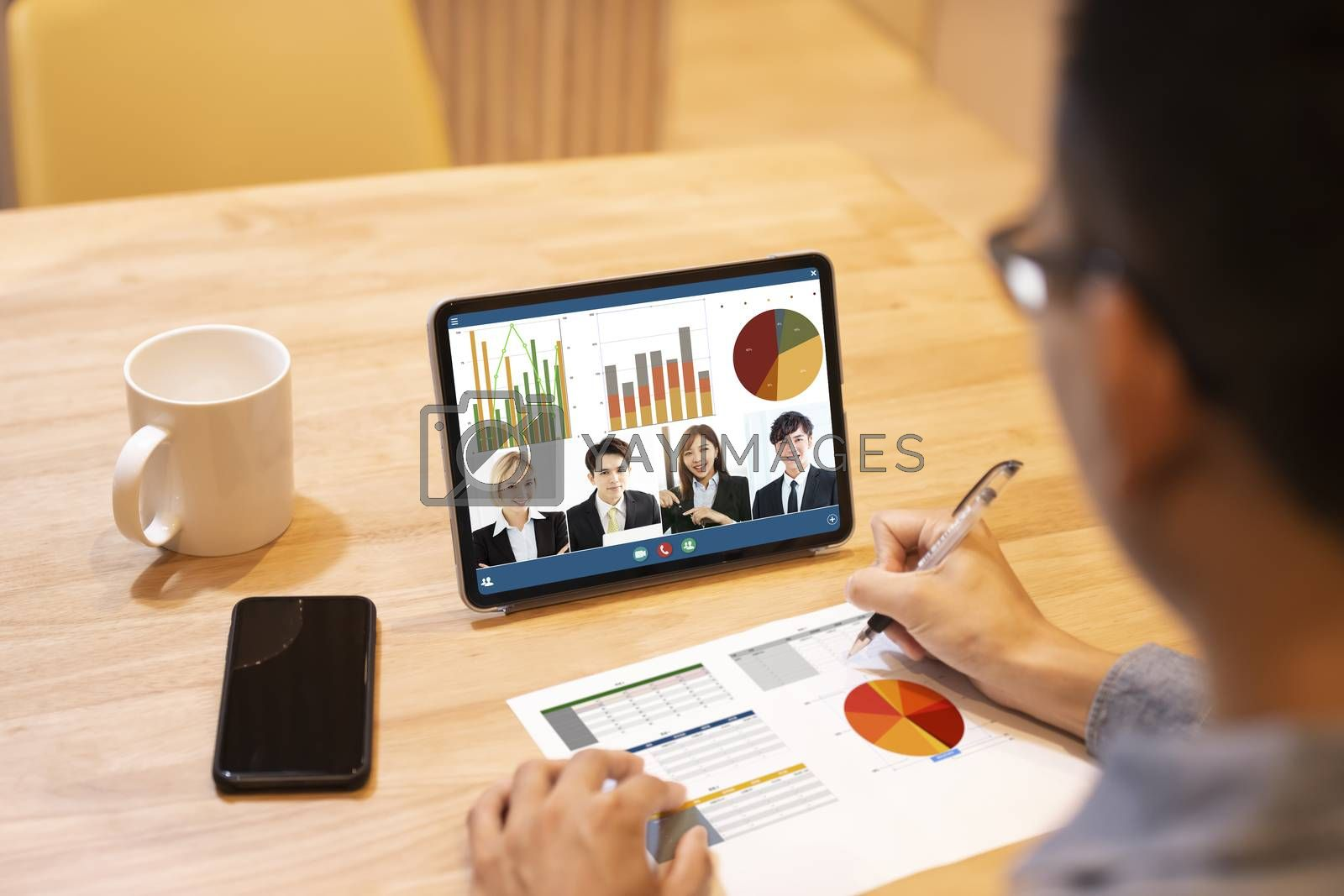 young man working at home and using tablet computer with video conference