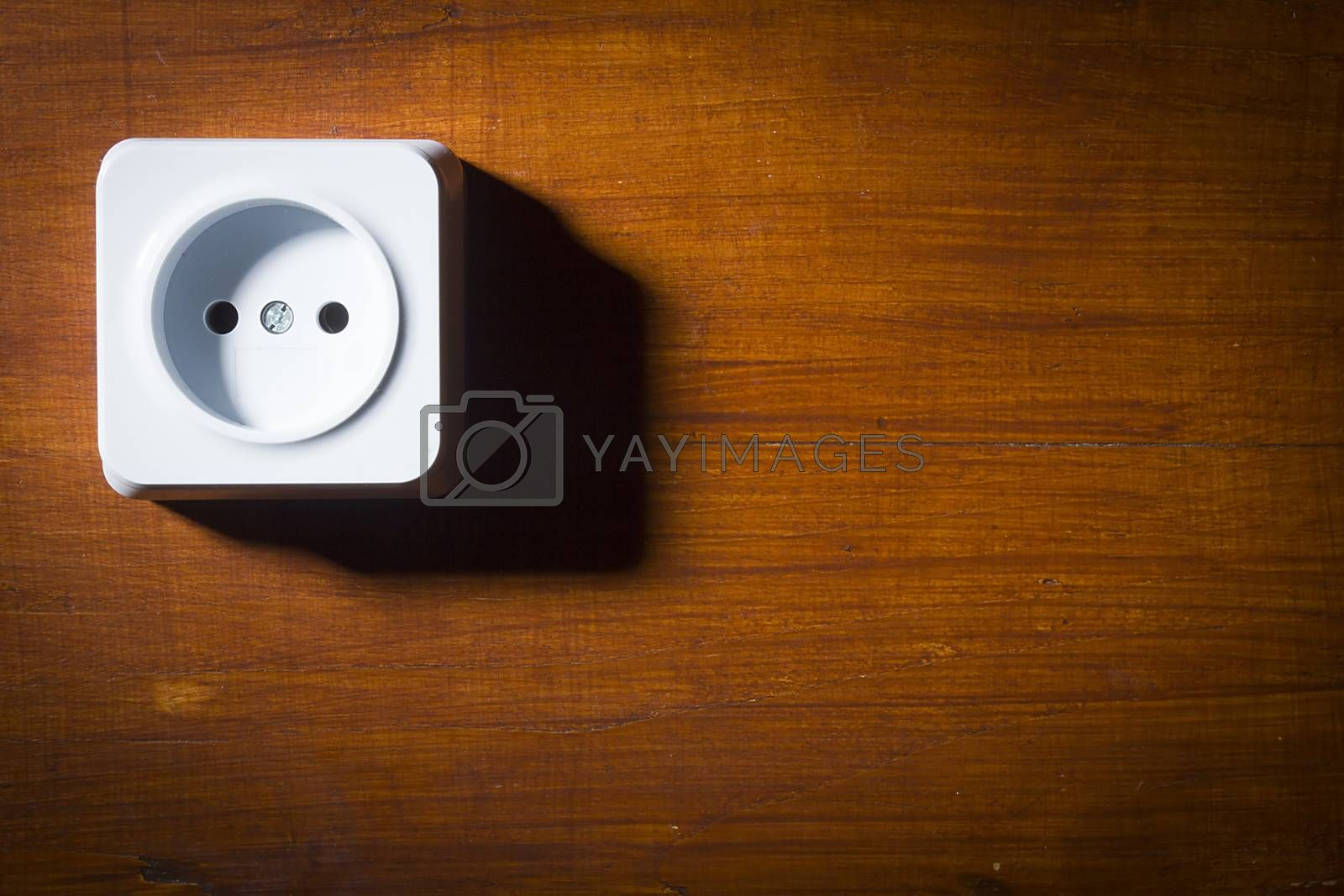 White plastic electrical outlet on a wooden wall