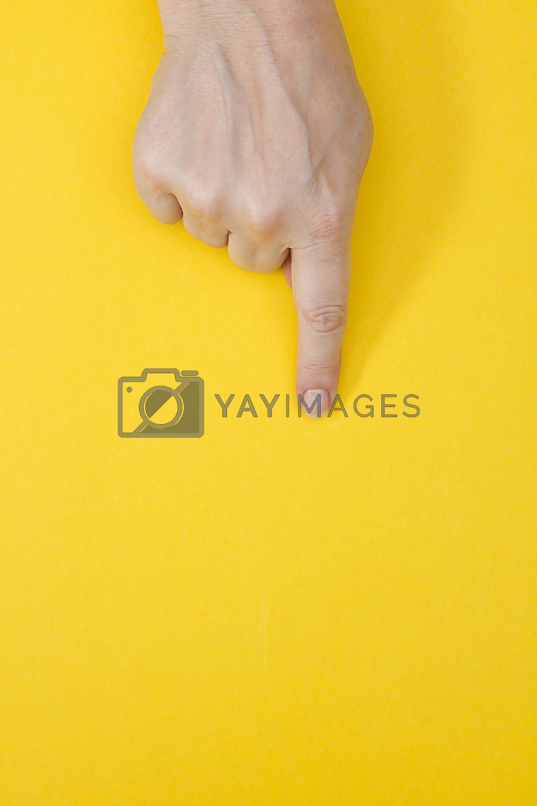 Woman's hand touching virtual screen on yellow background