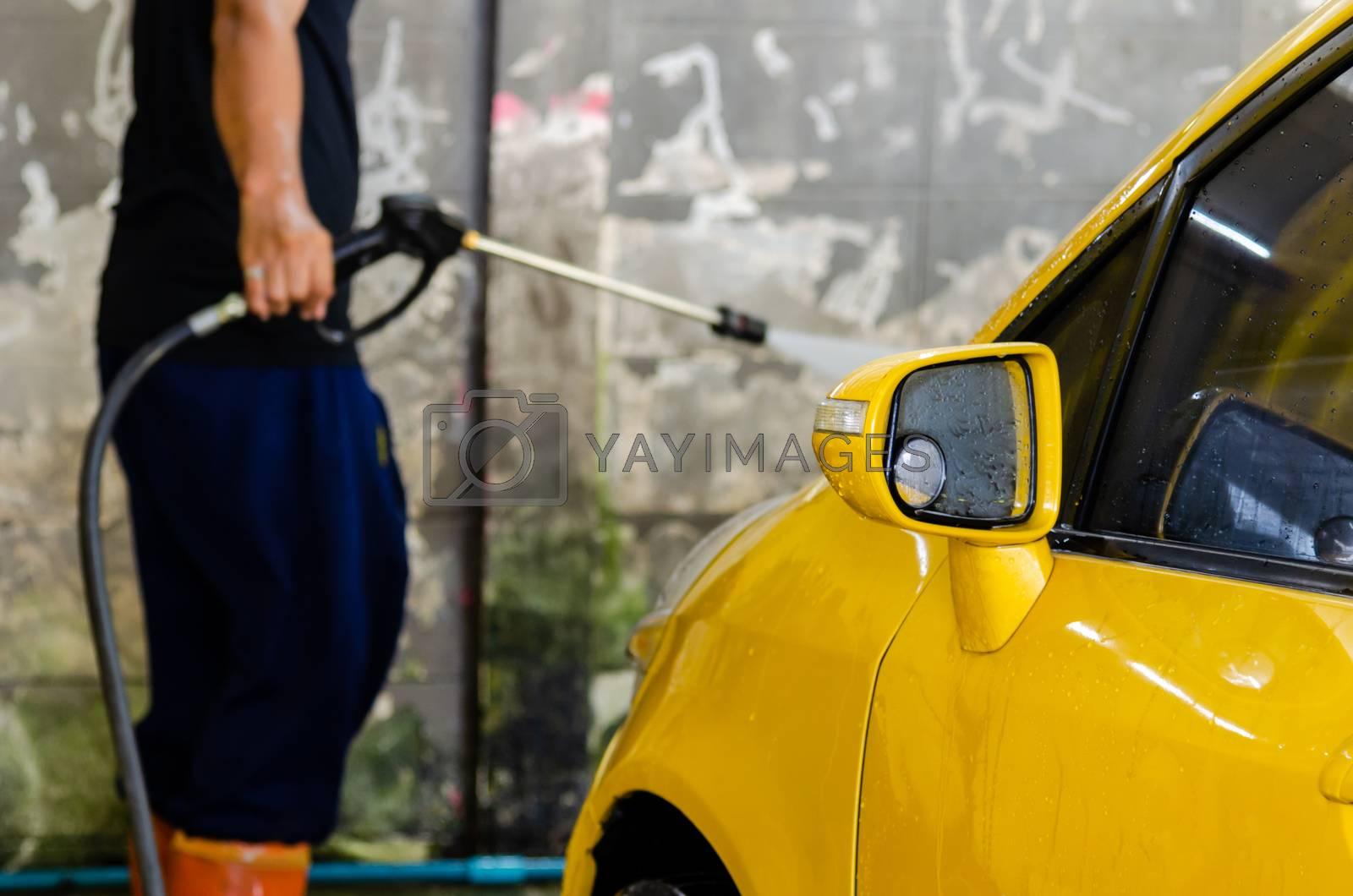 man with a high pressure car wash water gun.Yellow cars are washing cars at Car Care.