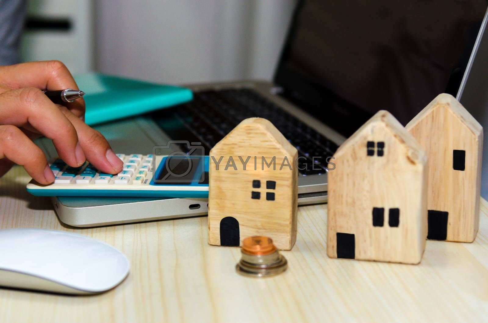 A small wooden house on the desk A man with a pen and a laptop computer and calculator Real estate business concept Property insurance.