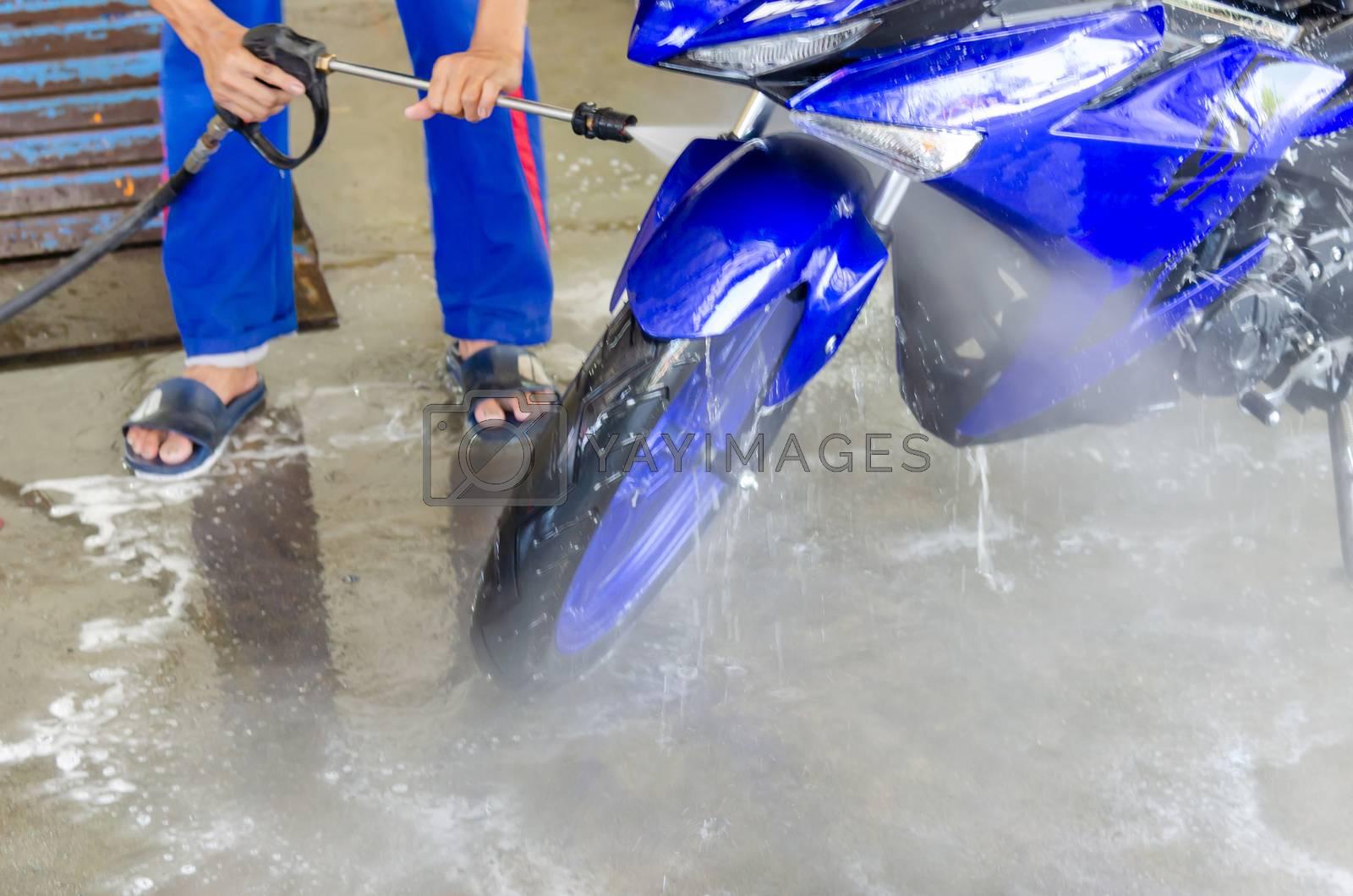 High-pressure water gun washing a motorcycle