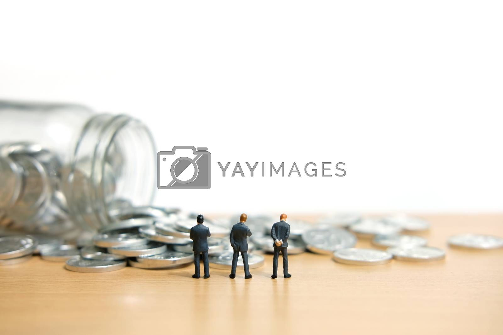 Group businessmen standing watching scattered money from a bottle. Miniature people figure conceptual photography.