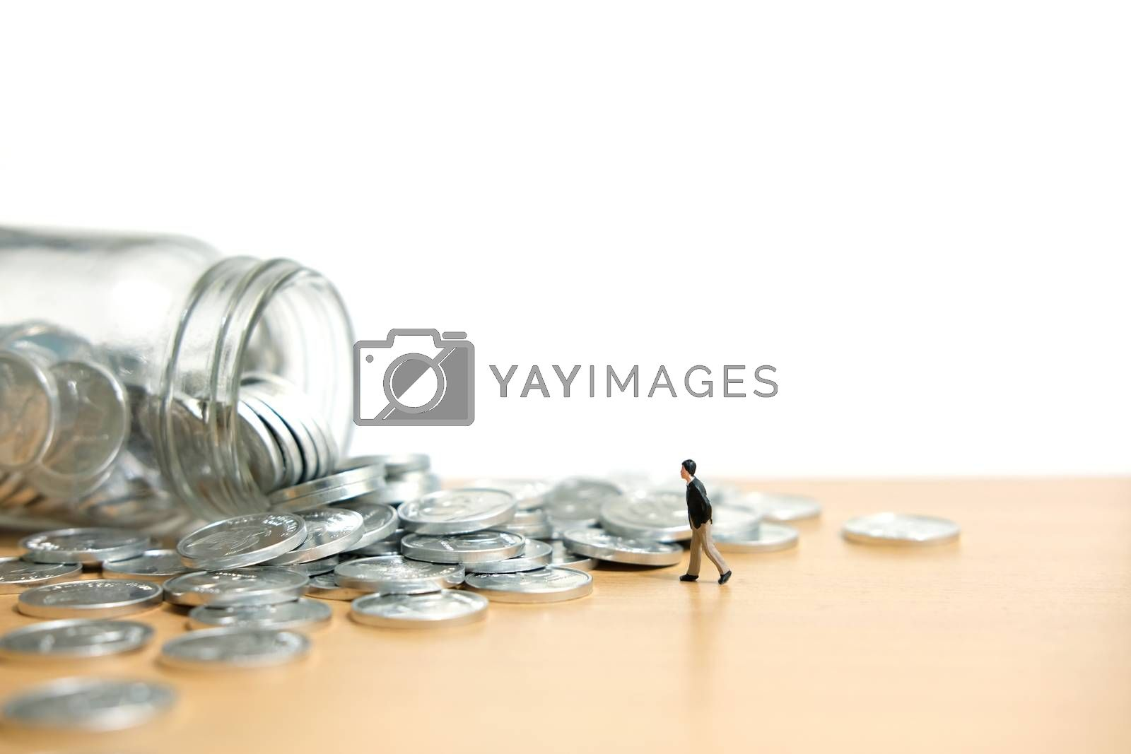A businessmen walking on coin stack - Financial saving. Miniature people figure conceptual photography.