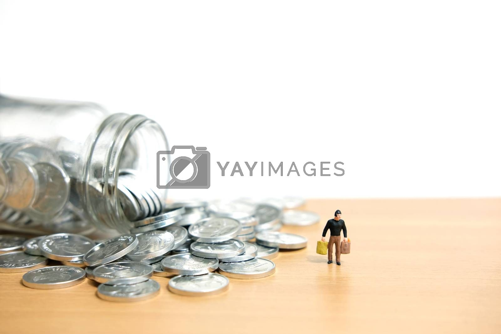 monthly expenditure - Men spend savings to shop. Miniature people figure conceptual photography.