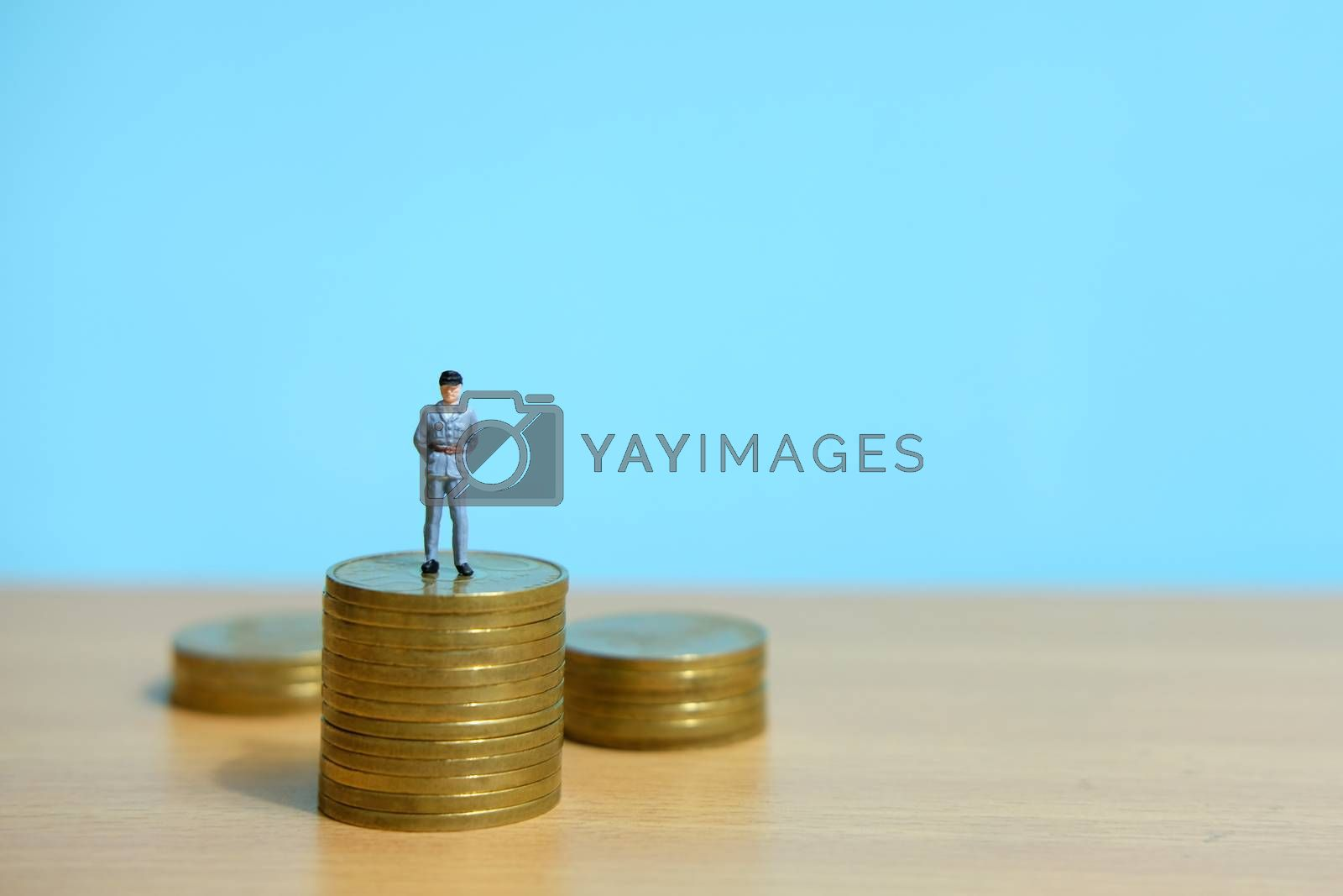 Policeman standing above coin stack to protect money. Miniature people figure conceptual photography.
