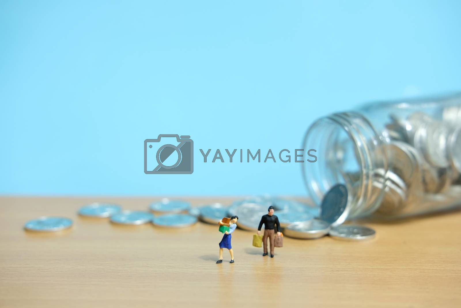 monthly expenditure, women and men spend savings to shop. Miniature people figure conceptual photography.