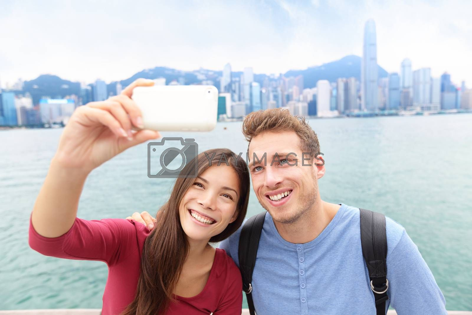 Selfie - friends taking self-portrait picture photo in Hong Kong enjoying sightseeing on Tsim Sha Tsui Promenade and Avenue of Stars in Victoria Harbour, Kowloon, Hong Kong. Travel concept.