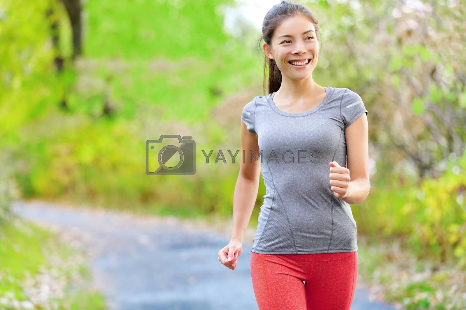 Woman nordic speed power walking, jogging and running lightly in forest in spring or summer. Sport fitness girl sports training and working out living healthy active lifestyle in forest.