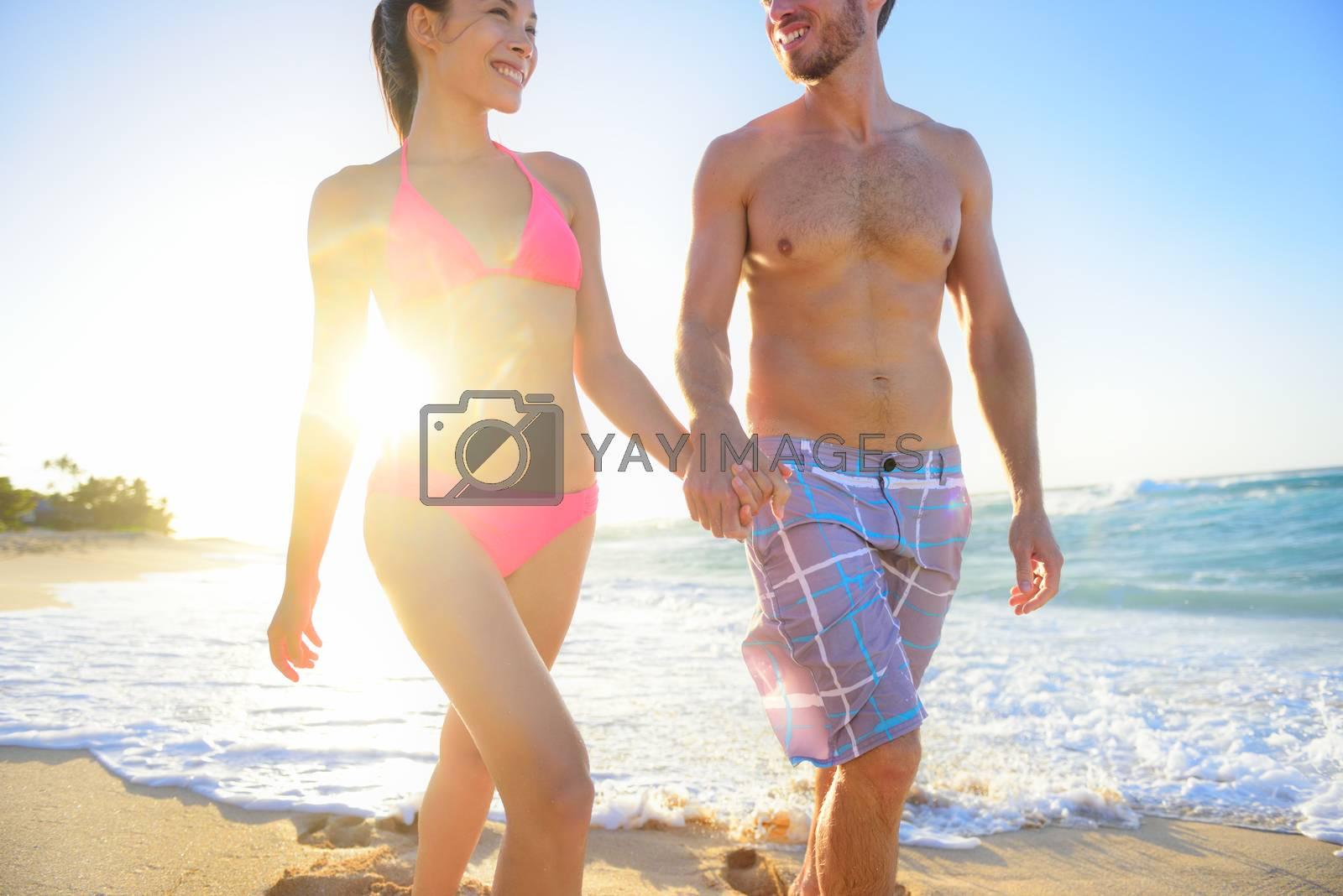 Mixed race couple walking holding hands happily smiling at beach sunset waterfront, enjoying summer honeymoon travel vacation. Hawaii