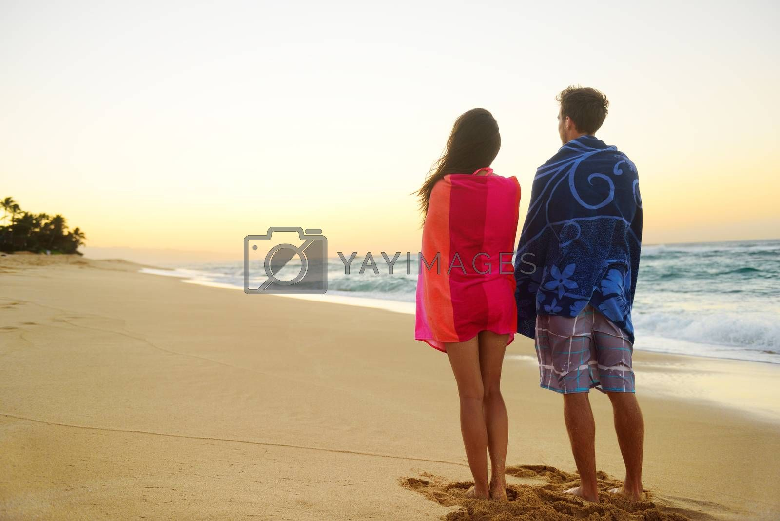 Couple standing in beach sand, towels over shoulders enjoying ocean sunset during travel holidays getaway vacation. Mixed race couple, asian woman, caucasian man.