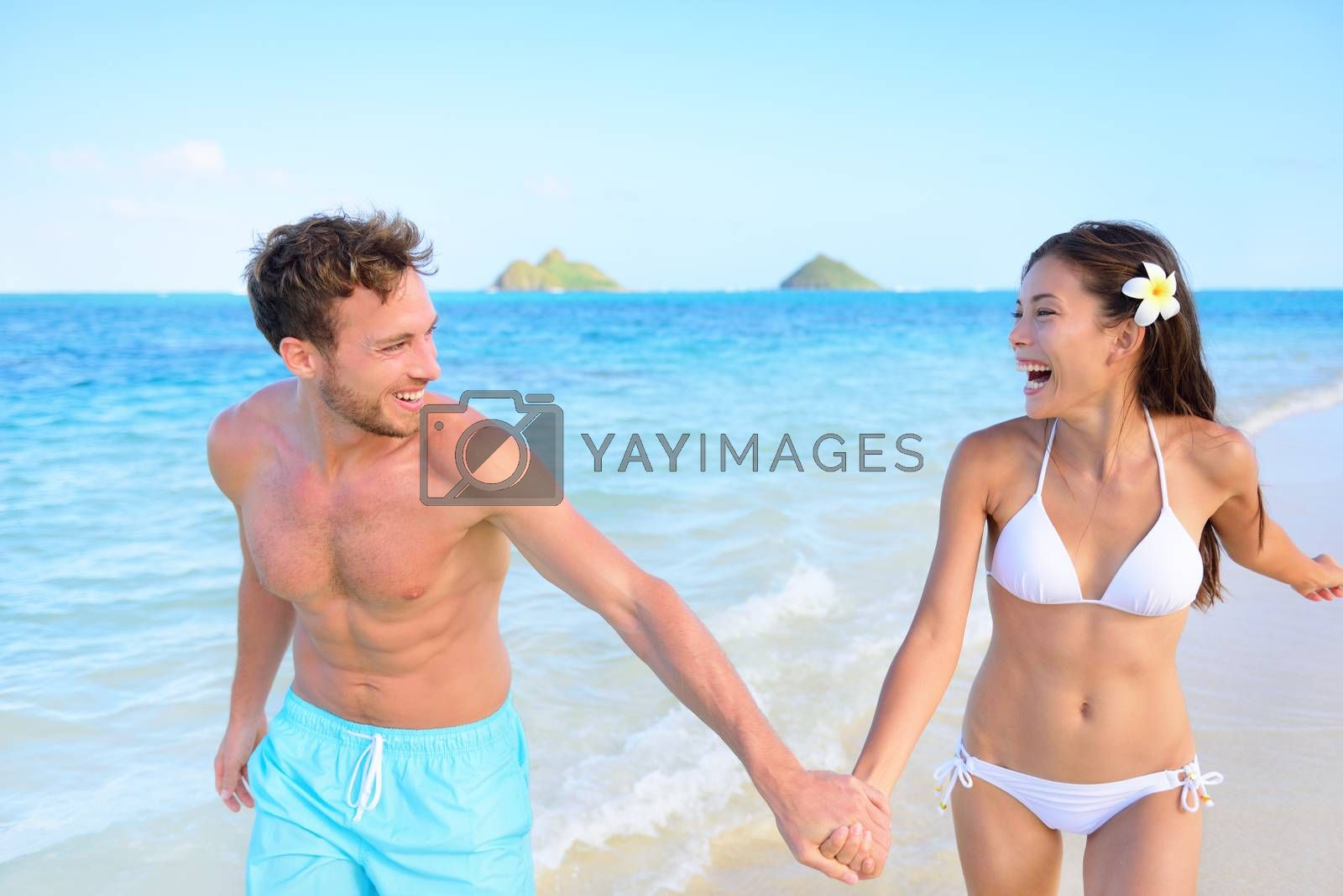 Fun on beach - couple in a happy relationship running together on a hawaiian beach during holidays travel vacation. Mixed race asian chinese woman and Caucasian man holding hands in trust in the sun.