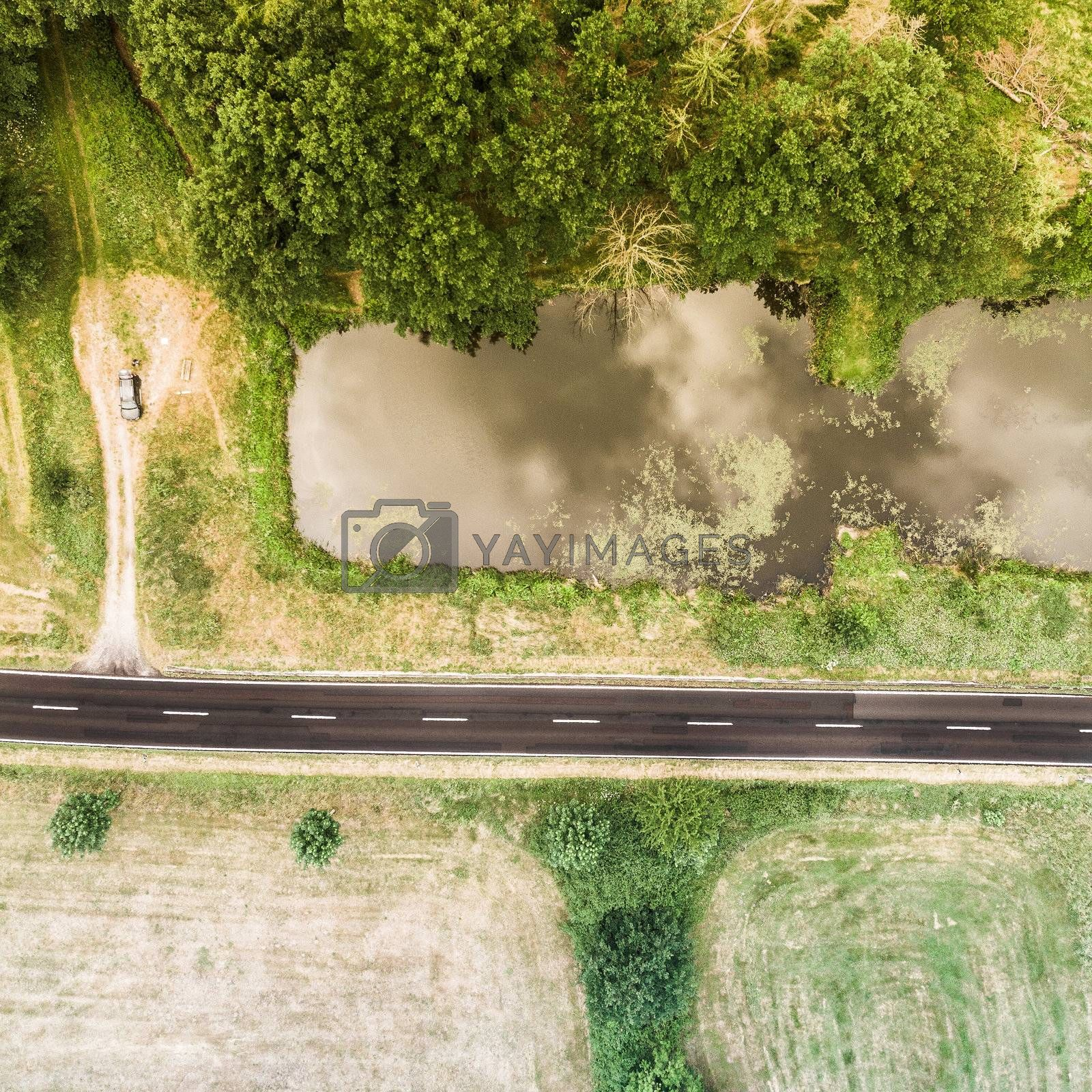 Aerial view of a small pond parallel to a country road in Saxony-Anhalt with fields and forests in the surrounding area, made with drone