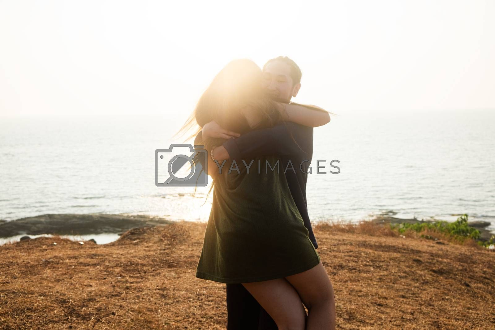 Backlit Portrait of a young romantic couple swirls in a hug against the backdrop of the sea. Anjuna Hills, Goa, India