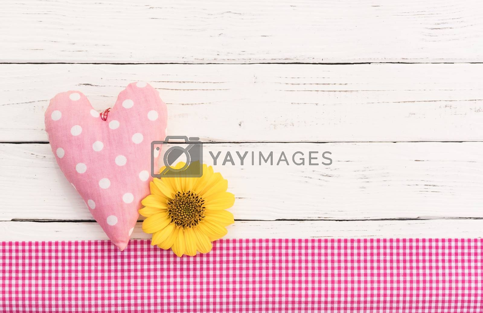 Romantic love background with pink heart and yellow blossom on white wood with copy space