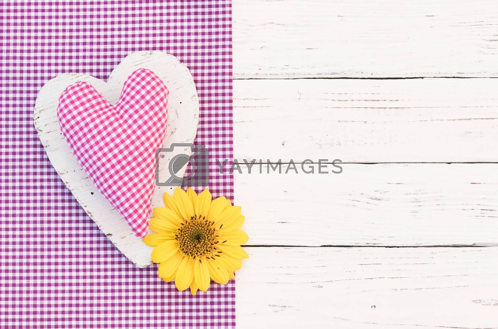 Romantic pink heart with yellow flower on white wooden background with copy space