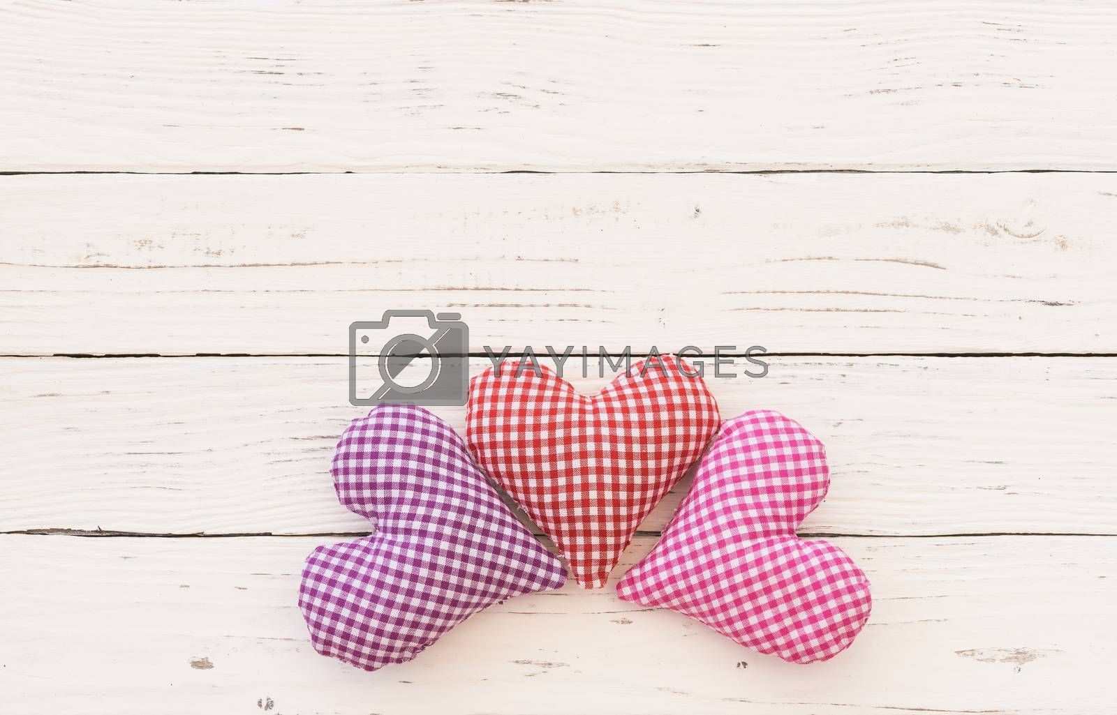 Valentine background with fabric hearts border on white wood and copy space