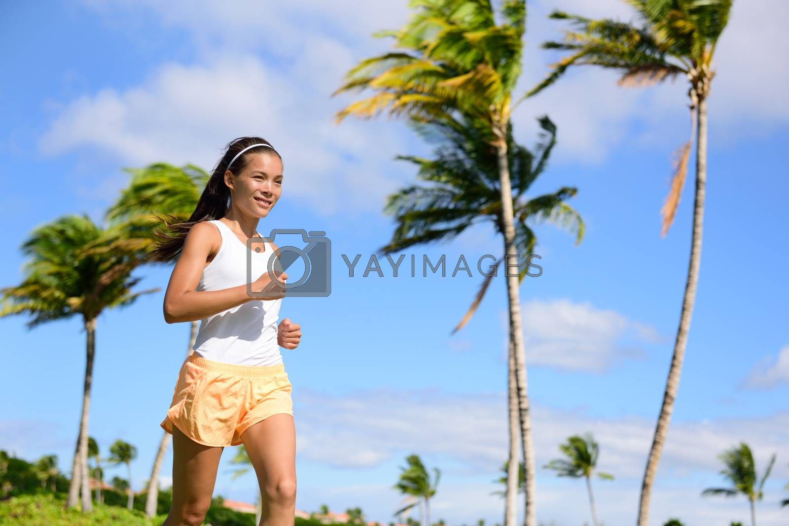 Asian runner girl jogging in tropical nature park outdoors with palm trees background during summer. Young adult sport woman running staying fit wearing orange fitness shorts and tank top.