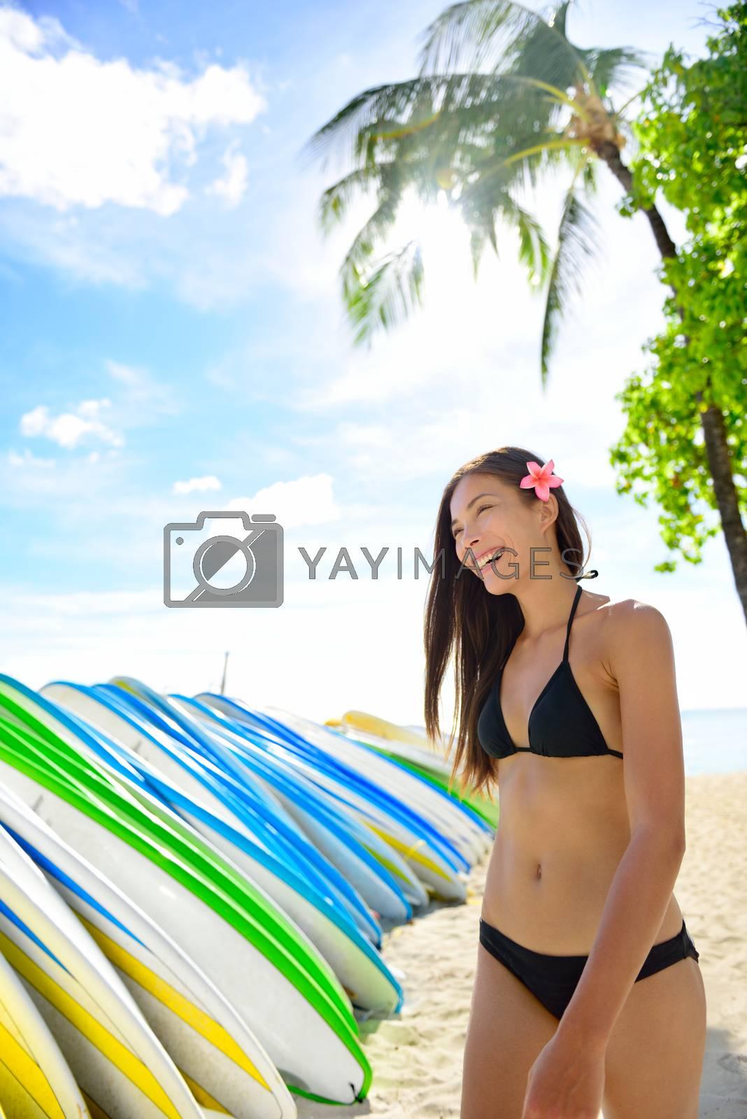 Bikini beach woman at surfboard rental surf shop. Happy Asian girl walking next to rack of many surf boards to rent for surf class on famous Waikiki beach, Honolulu City, Oahu, Hawaii, USA.