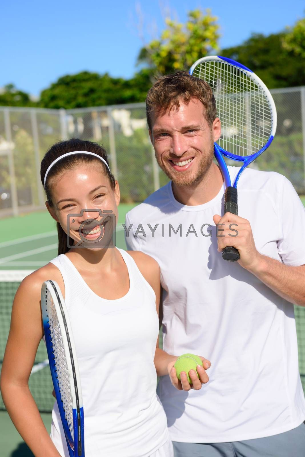 Tennis sport - Mixed doubles couple players portrait relaxing after playing game outside in summer. Happy smiling people on outdoor tennis court living healthy active lifestyle. Woman and man athletes