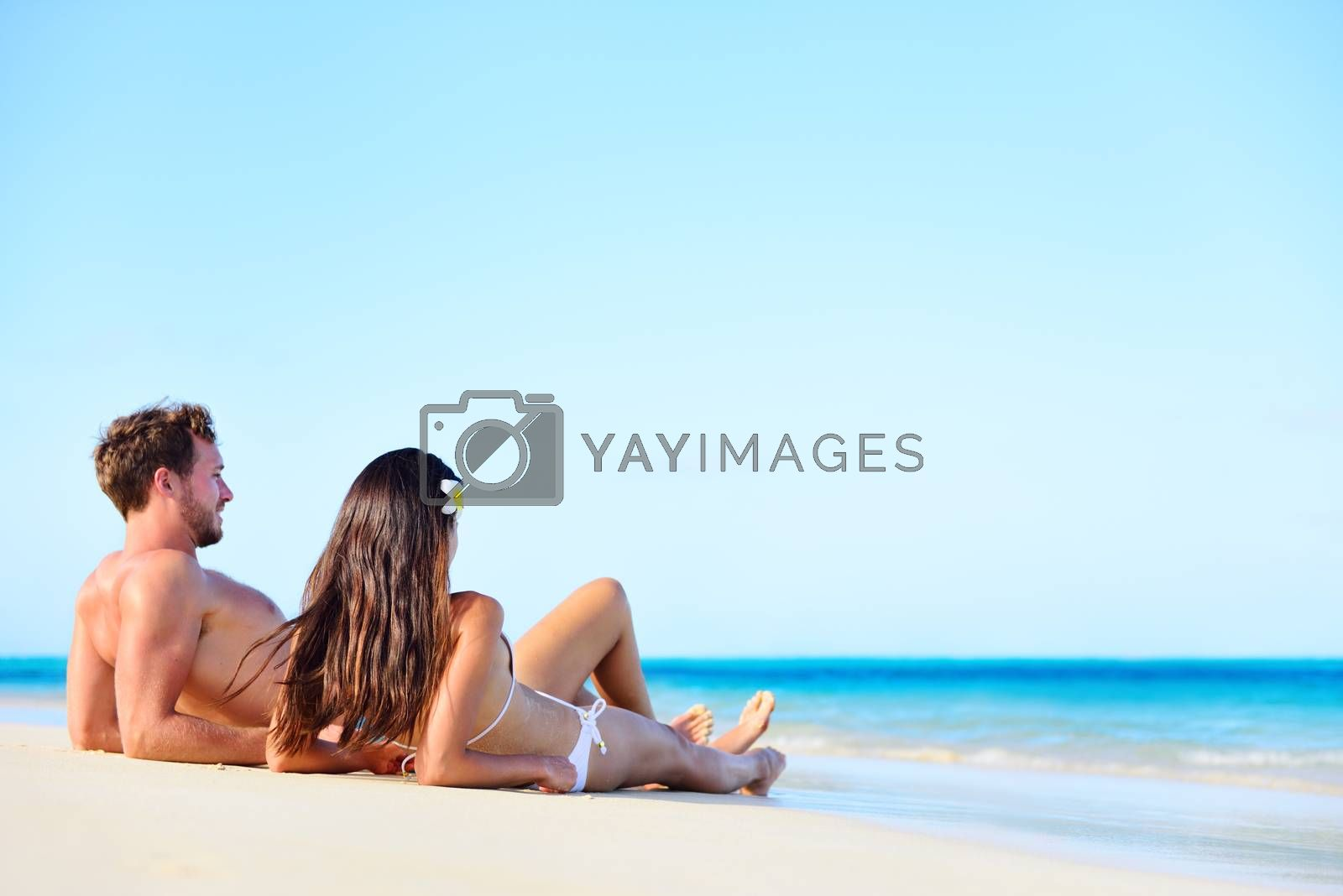 Beach vacation couple relaxing tanning in summer. Beautiful young adults on holidays lying down on white sand enjoying travel getaway under blue sky by turquoise water ocean sea. Multiracial couple.