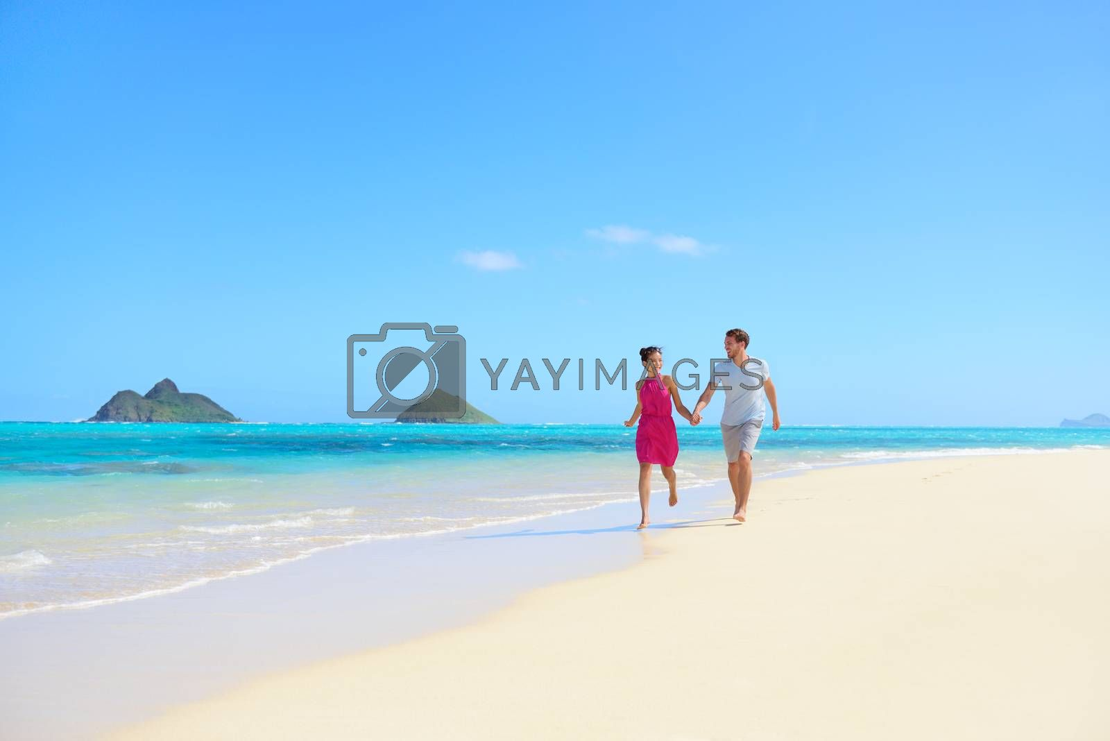 Beach couple happy having fun on Hawaii honeymoon. Romantic couple cheerful and full of happiness on travel vacation on Lanikai beach, Oahu, Hawaii, USA with Mokulua Islands. Asian woman, Caucasian man