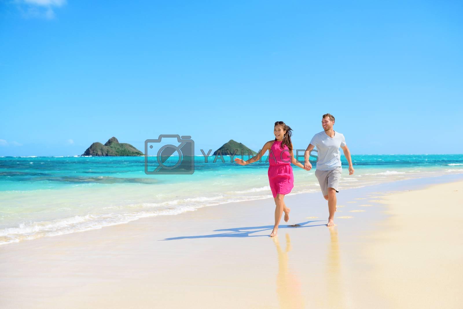 Beach happy couple on running having fun on Hawaii. Romantic couple joyful and full of happiness on travel vacation on Lanikai beach, Oahu, Hawaii, USA with Mokulua Islands. Asian woman, Caucasian man